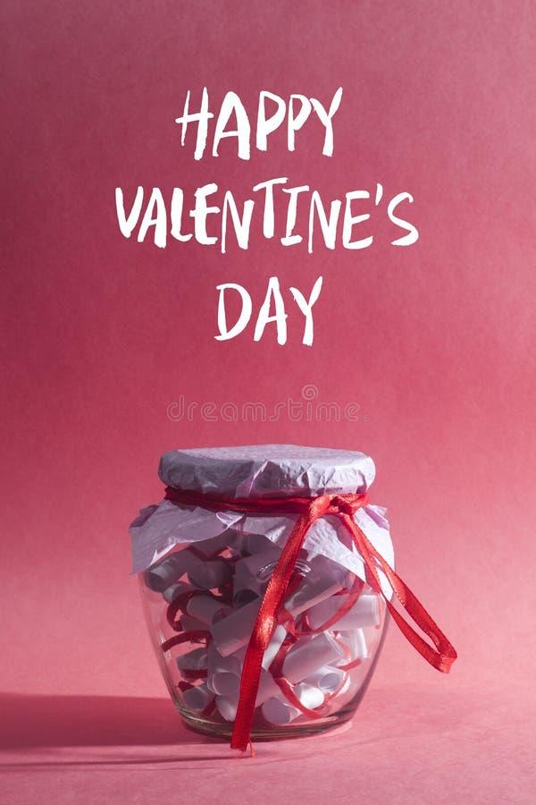 Glücklicher Valentinsgruß `s Tag Glasgefäß, voll von gerollten Papieren mit süßen Träumen lizenzfreies stockfoto