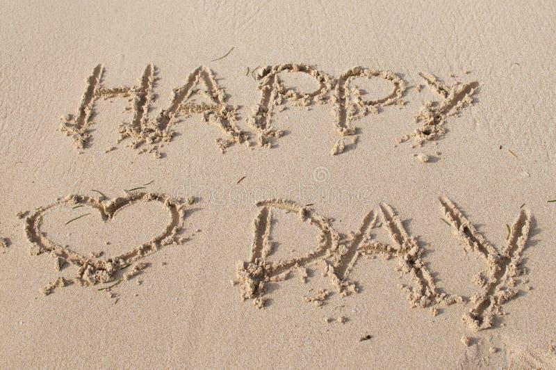 Glücklicher Valentinstagtext geschrieben auf den Sand stockbild