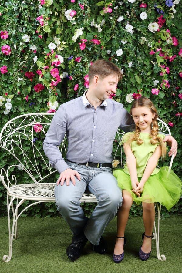 Glücklicher Vater betrachtet die kleine Tochter, die auf Retro- Bank sitzt stockbild