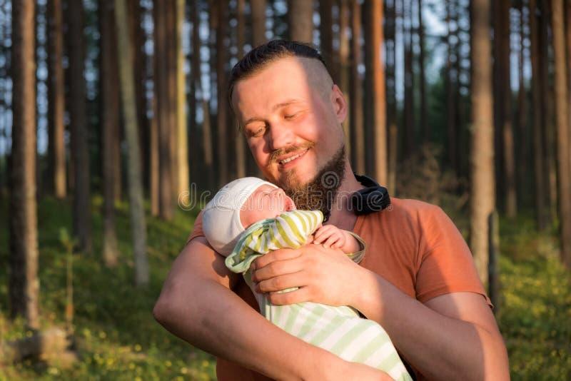 Glücklicher Vater betrachtet seinen netten kleinen schlafenden Sohn mit Liebe und Angebot beim ihn leicht halten stockfoto