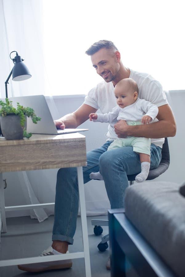 glücklicher Vater, der auf Stuhl sitzt, Baby hält und Laptop verwendet lizenzfreie stockfotografie