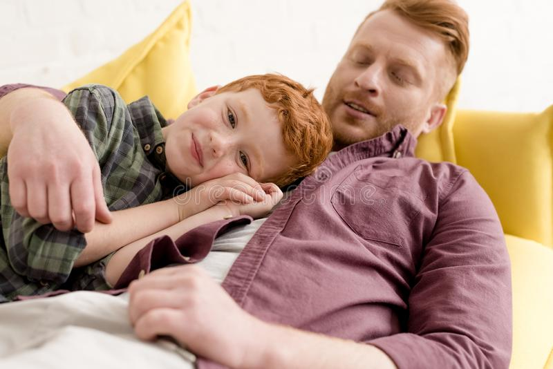glücklicher Vater, der den entzückenden kleinen Sohn lächelt an der Kamera umarmt lizenzfreie stockfotos