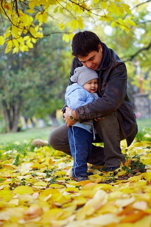 Glücklicher Vater, der kleinen Sohn im Herbstpark umarmt stockfotografie