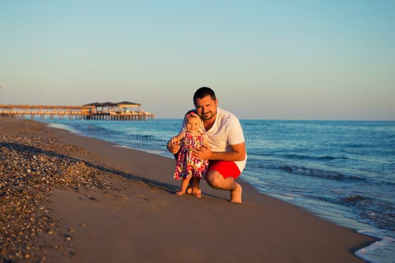 Glücklicher Vater, der mit netter kleiner Tochter am Strand spielt stockfotografie