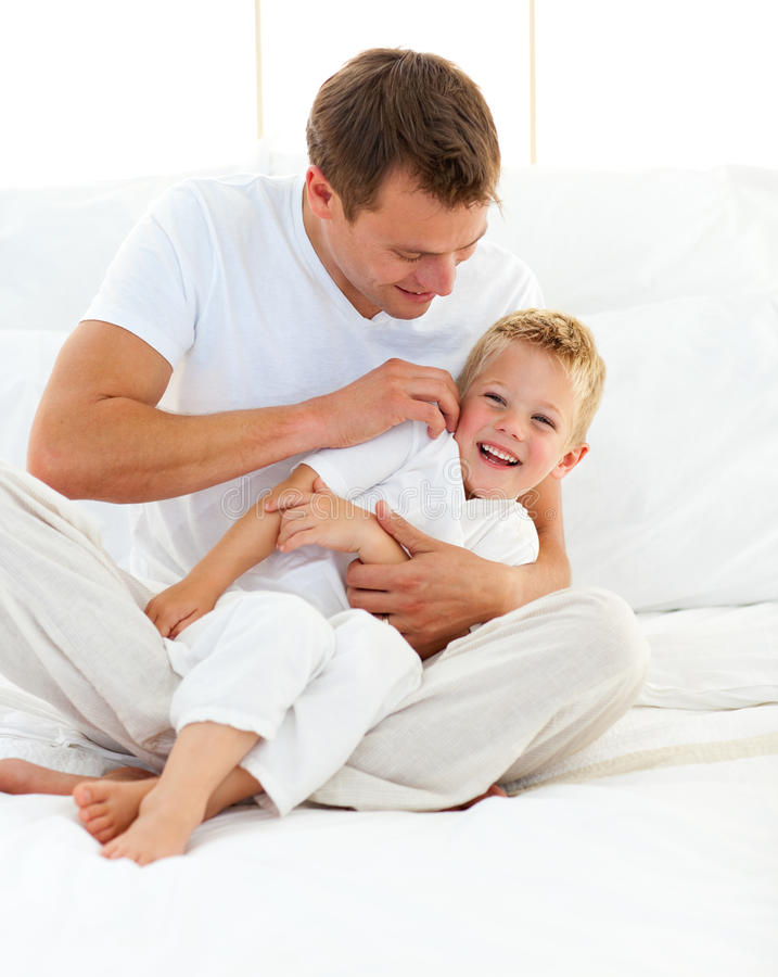 Glücklicher Vater, der mit seinem Jungen auf einem Bett spielt stockbild