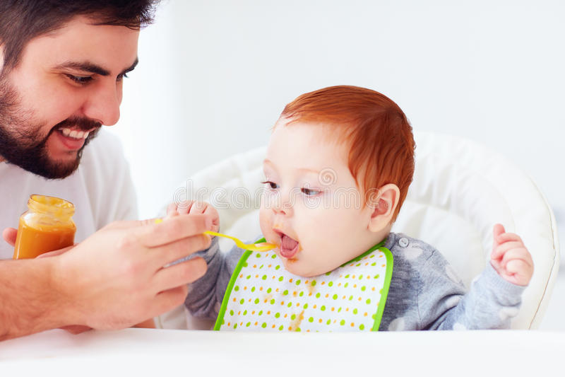 Glücklicher Vater, der nettes Rothaarigebaby mit ergänzendem Lebensmittel einzieht stockfotos