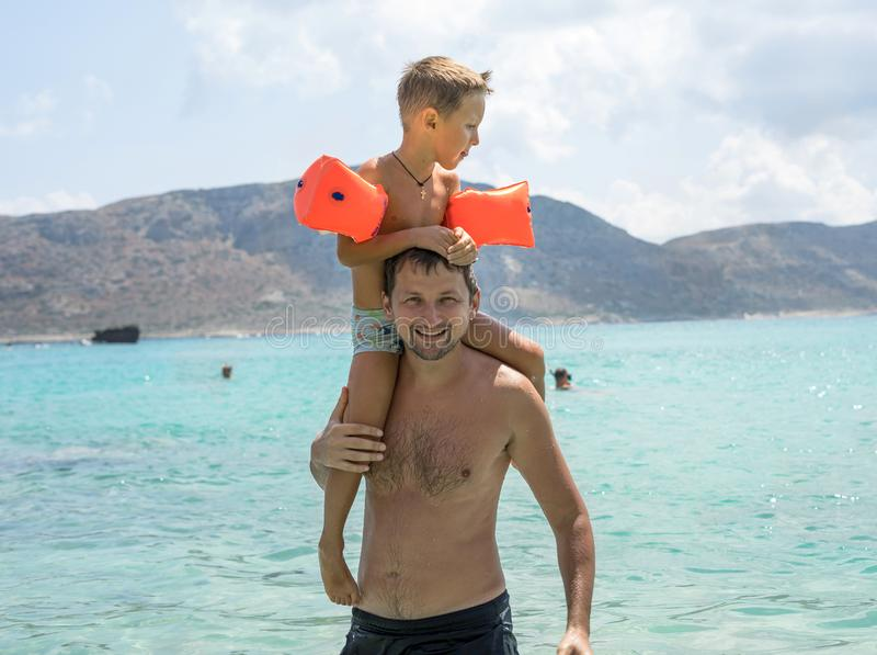 Glücklicher Vater, der Schulterfahrt auf seine Schultern am Strand gibt Glücklicher lächelnder Junge auf dem Schultervati, der Ka stockbild