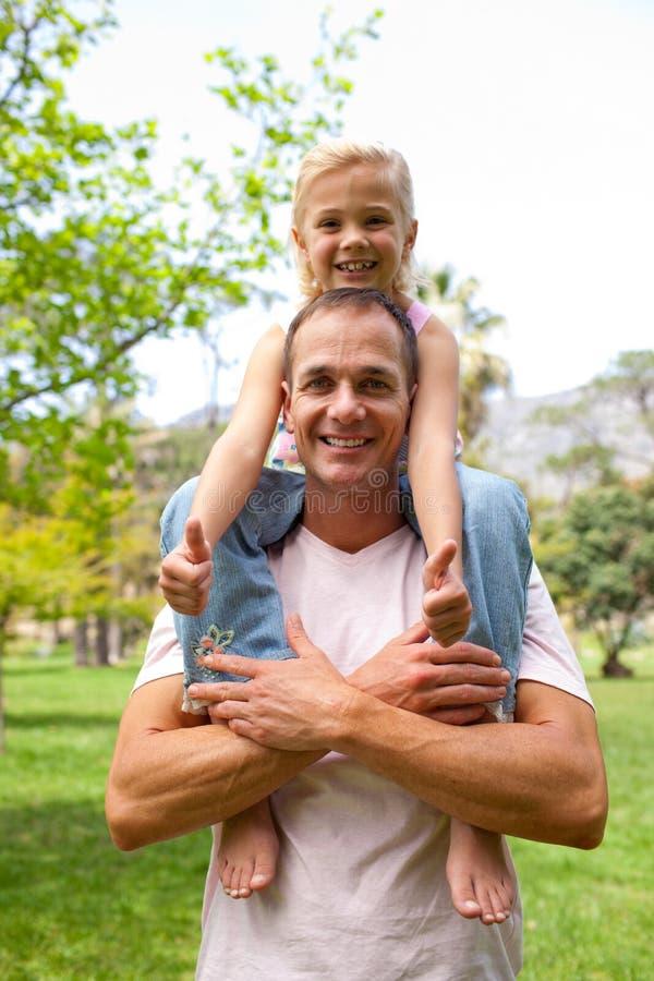 Glücklicher Vater, der seine Tochterdoppelpolfahrt gibt stockfotos