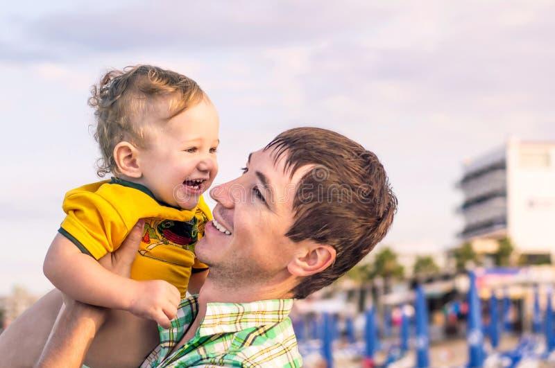 Glücklicher Vater, der wenig glücklichen Sohn in seinen Armen hält lizenzfreies stockfoto