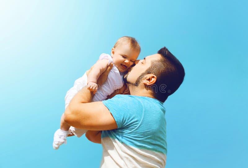 Glücklicher Vater des Lebensstilfamilienfotos, der draußen Baby küsst stockbild