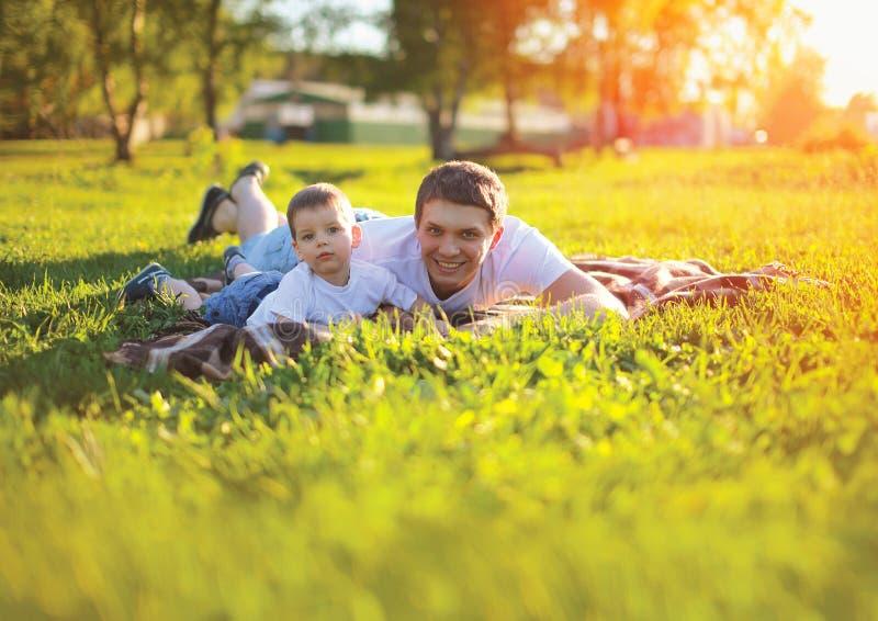 Glücklicher Vater des sonnigen Porträts mit dem Sohnkind, das auf dem Gras liegt stockbild
