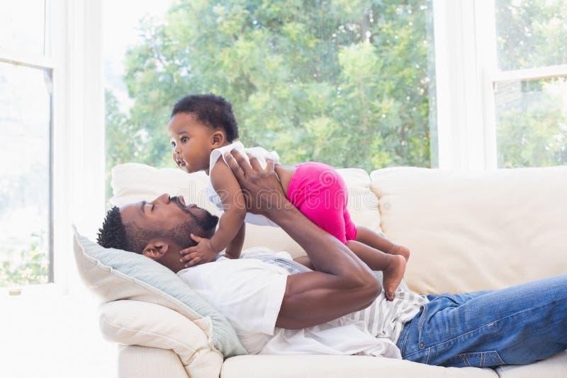 Glücklicher Vater mit Baby auf Couch lizenzfreies stockbild