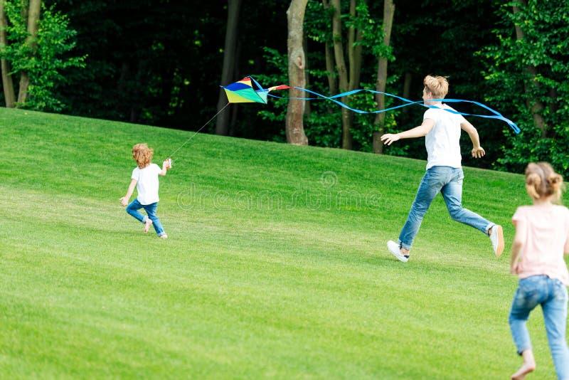glücklicher Vater mit der Tochter und Sohn, die mit Drachen beim Laufen auf grüner Wiese spielen stockfoto