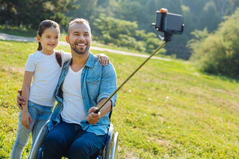 Glücklicher Vater mit der Unfähigkeit, die ein selfie mit Tochter nimmt lizenzfreie stockbilder