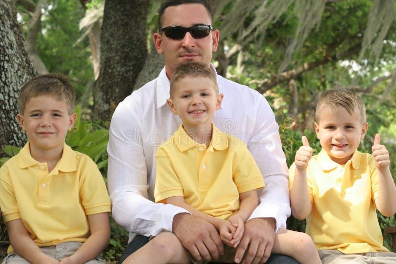 Glücklicher Vater mit drei Söhnen stockbild