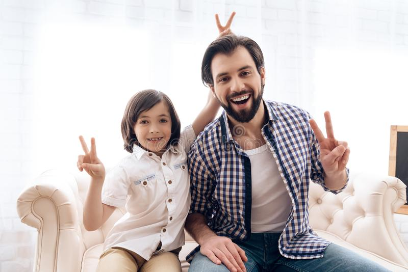 Glücklicher Vater mit Sohn zeigt Zeichen des Sieges stockbilder