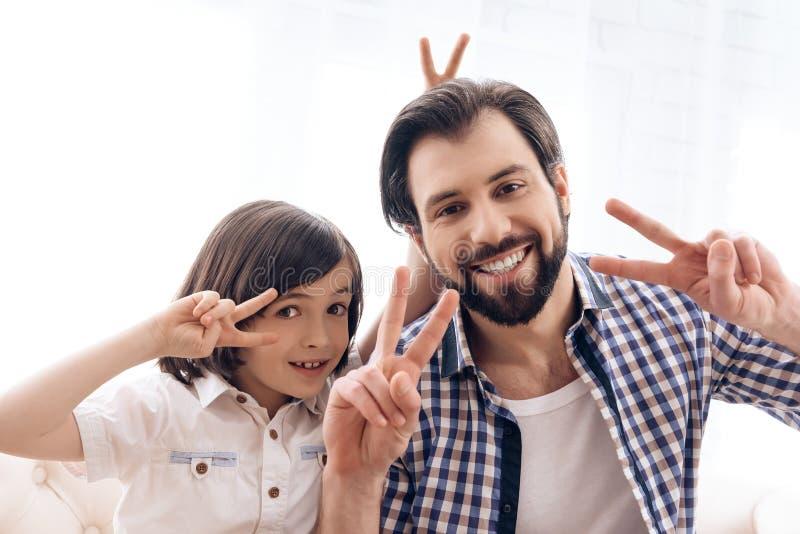 Glücklicher Vater mit Sohn zeigt Zeichen des Sieges lizenzfreie stockfotos