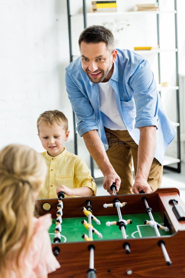 glücklicher Vater mit zwei entzückenden Kindern, die Tischfußball spielen stockfoto