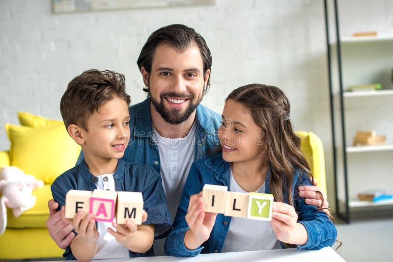 glücklicher Vater mit zwei entzückenden Kindern, die Würfel halten stockfotos