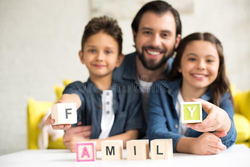 glücklicher Vater mit zwei entzückenden Kindern, die Würfel mit Wortfamilie und -c$lächeln halten lizenzfreies stockbild