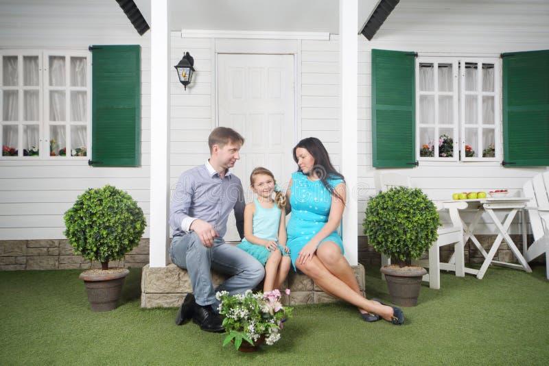 Glücklicher Vater, Mutter und Tochter sitzen auf Portal lizenzfreies stockbild