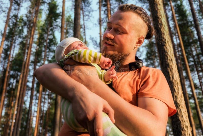 Glücklicher Vater schaut auf seinem netten kleinen schlafenden Sohn mit Liebe und Angebot lizenzfreie stockfotografie