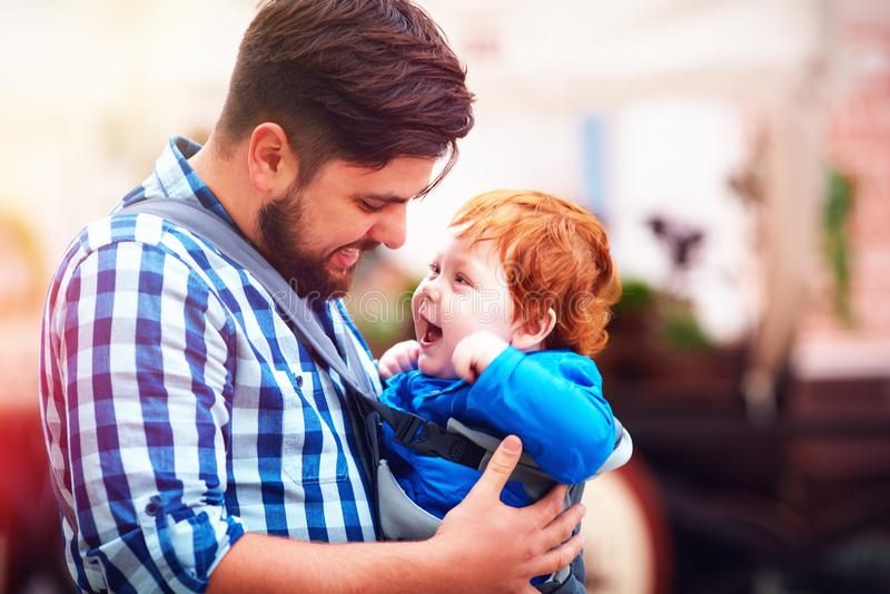 Glücklicher Vater- und Babysohn im Riemen wandern Haben eines Wegs in der Stadt lizenzfreie stockfotografie