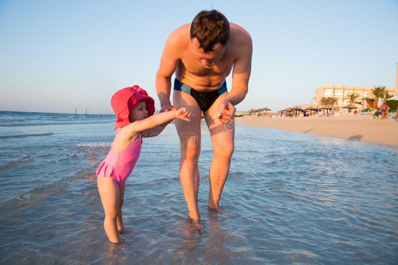 Glücklicher Vater und entzückendes kleines Mädchen am Strand Persischer Golf, Dubai lizenzfreie stockbilder