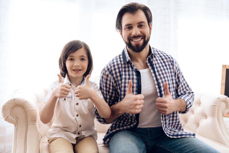 Glücklicher Vater- und Jugendlichsohn, der sich Daumen zeigt lizenzfreie stockbilder