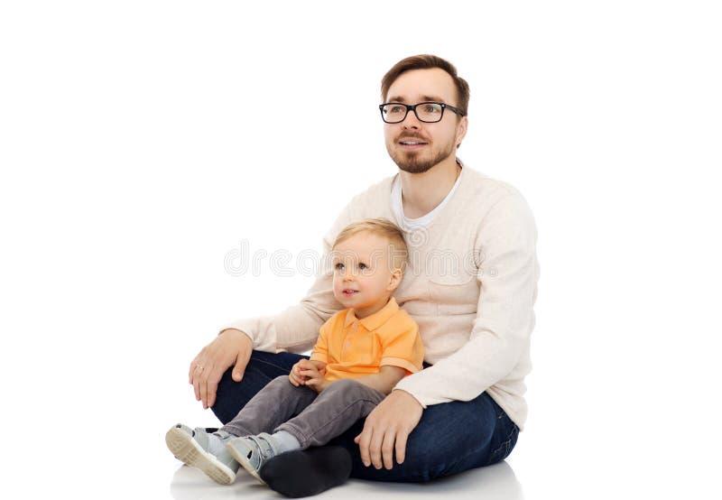 Glücklicher Vater und kleiner Sohn, die zusammen sitzt stockbild
