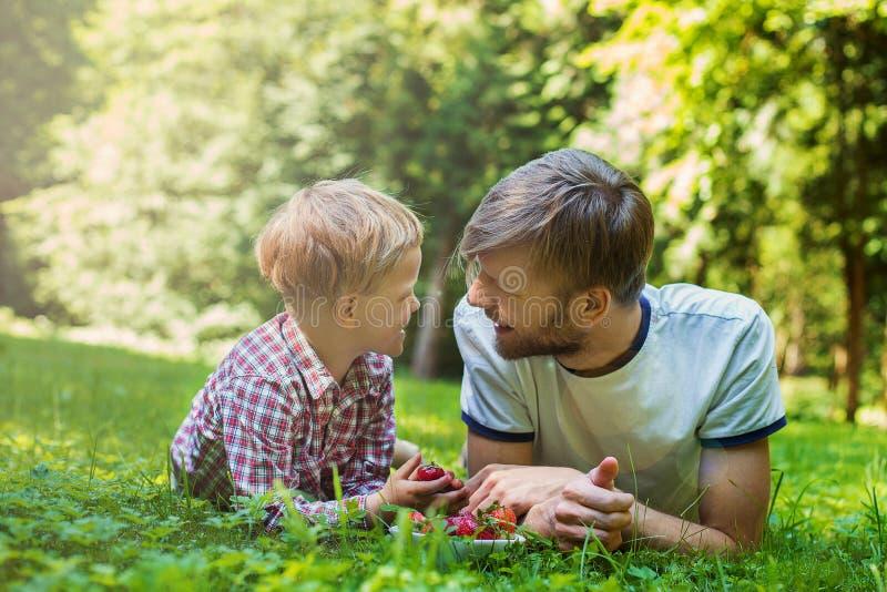 Glücklicher Vater und Sohn des Sommerfotos, die zusammen auf grünem Gras liegt stockfotografie