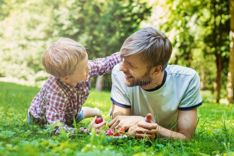 Glücklicher Vater und Sohn des Sommerfotos, die zusammen auf grünem Gras liegt lizenzfreies stockfoto