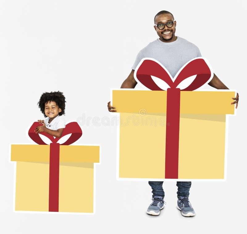 Glücklicher Vater und Sohn, die Geschenkboxen hält lizenzfreie stockbilder