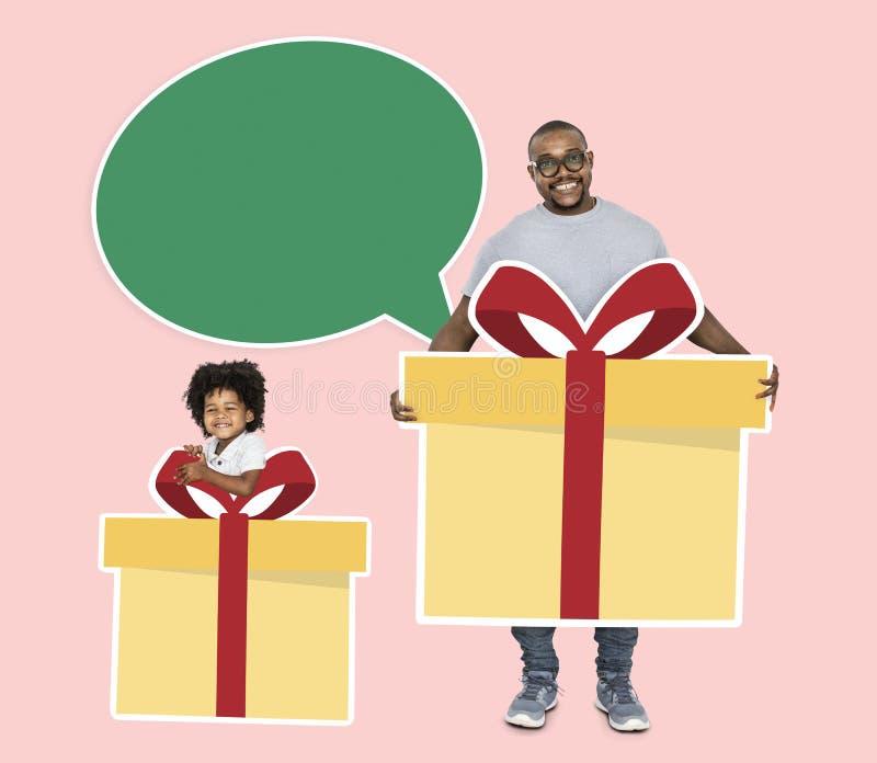 Glücklicher Vater und Sohn, die Geschenkboxen hält stockfotografie