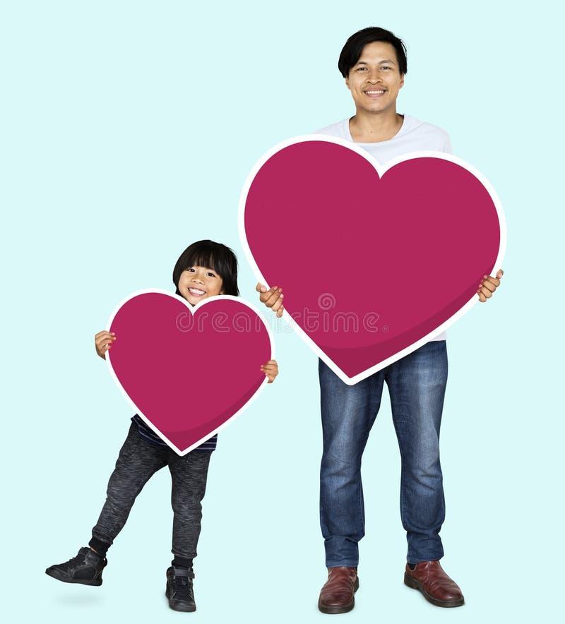 Glücklicher Vater und Sohn, die Herzen hält lizenzfreies stockfoto