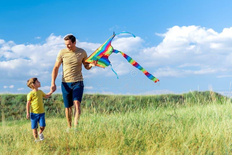 Glücklicher Vater und Sohn, die mit Drachen in der Natur spielt lizenzfreies stockfoto