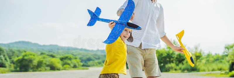 Glücklicher Vater und Sohn, die mit Spielzeugflugzeug gegen alten Rollbahnhintergrund spielt Mit Kinderkonzept FAHNE reisen, LANG stockbild