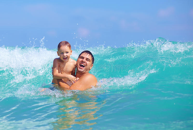 Glücklicher Vater und Sohn, die Spaß in den Wasserwellen hat lizenzfreie stockfotografie