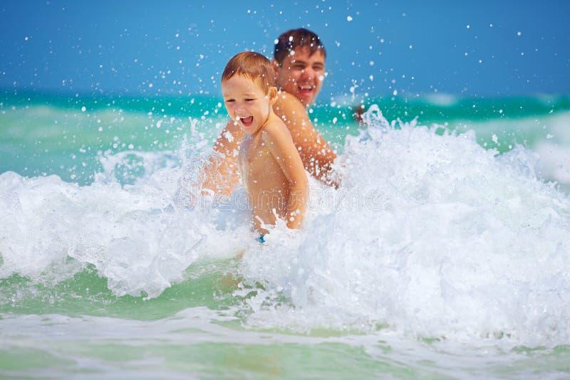 Glücklicher Vater und Sohn, die Spaß in den Wellen, Sommerferien hat stockfotografie
