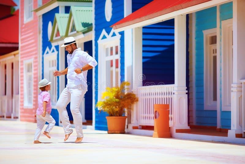 Glücklicher Vater und Sohn genießen das Leben und tanzen auf karibische Straße lizenzfreie stockfotos