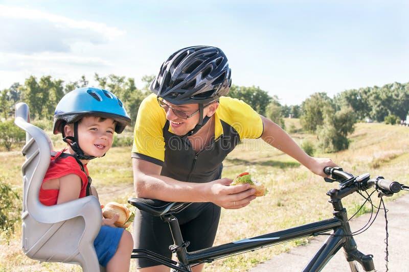 Glücklicher Vater und Sohn isst das Mittagessen (Snack) während der Fahrradfahrt stockbilder