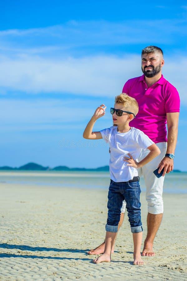 Glücklicher Vater und Sohn zur tropischen Strand-, zusammen lachen und Enjoingzeit lizenzfreie stockfotos