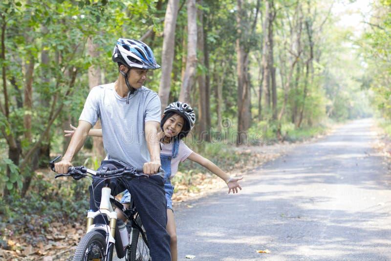 Glücklicher Vater und Tochter, die in den Park radfährt stockfotos