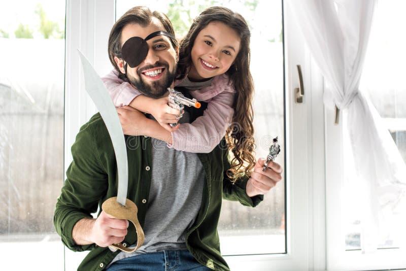 glücklicher Vater und Tochter, die an der Kamera beim zusammen spielen und Vortäuschen, Piraten zu sein lächelt stockfotografie