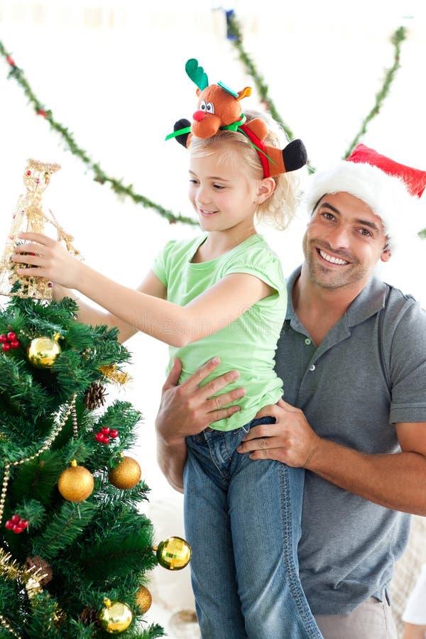 Glücklicher Vater, welche seiner verzierenden Tochter hilft lizenzfreies stockbild