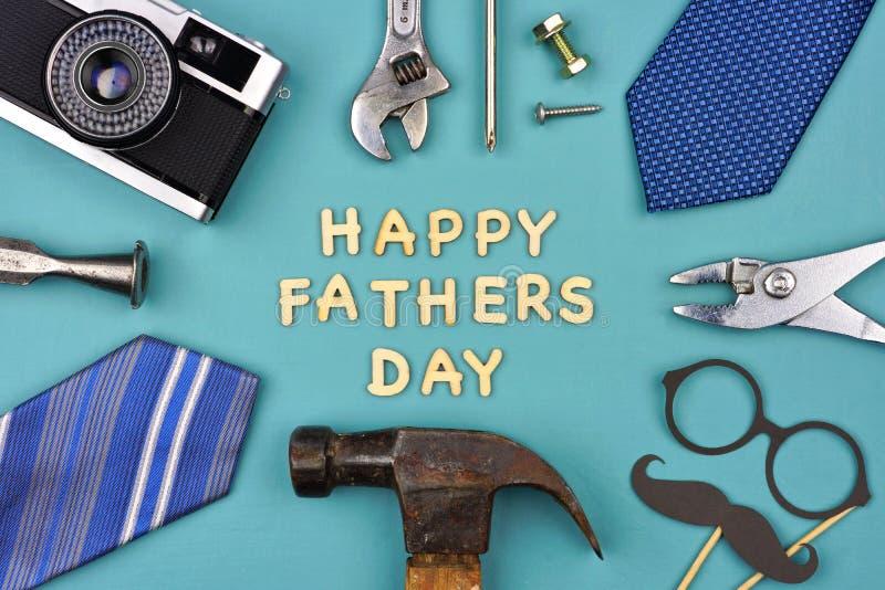 Glücklicher Vatertag mit Rahmen von Geschenken, von Dekor, von Bindungen und von Werkzeugen auf Blau lizenzfreie stockfotografie