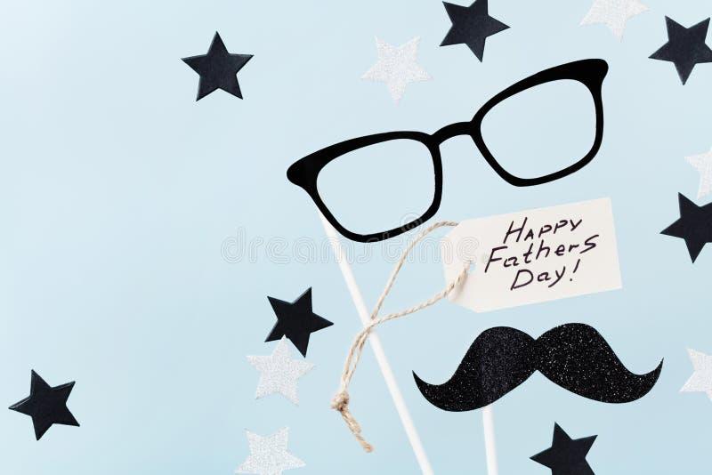 Glücklicher Vatertagshintergrund mit Grußtag, Gläsern, dem lustigen Schnurrbart und den Sternkonfettis auf Tischplatteansicht fla stockfotos