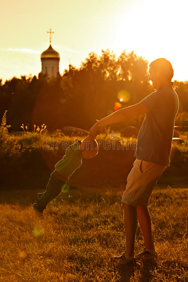 Glücklicher Vati, der mit seinem Sohn im Park auf einem Hintergrund der Kirche spielt lizenzfreie stockbilder