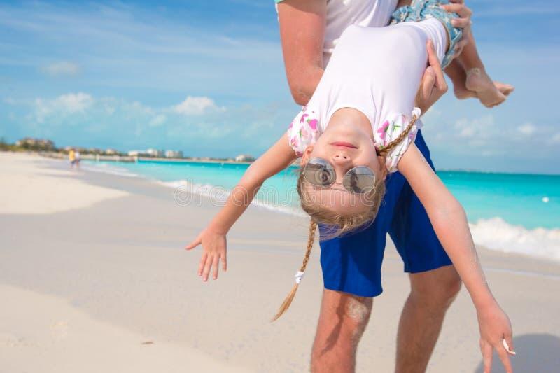 Glücklicher Vati haben Spaß mit seinem kleinen netten Mädchen am perfekten Strand stockbilder