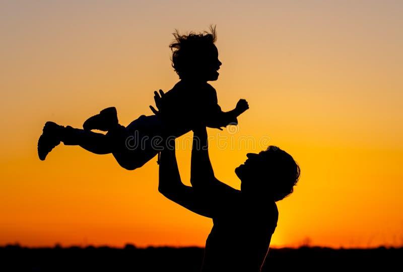 Glücklicher Vati wirft das Kleinkind bei Sonnenuntergang Glückliches Familienkonzept Little Boy stockfotografie